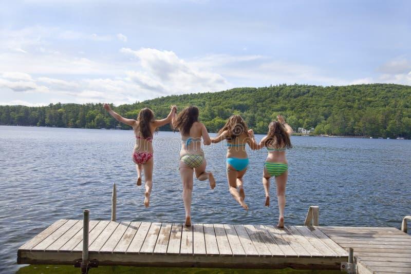 跳湖的码头四女孩少年 免版税库存图片