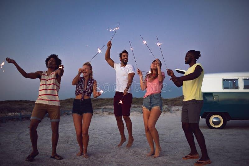 跳舞与在海滩的闪烁发光物的小组朋友在黄昏 免版税图库摄影