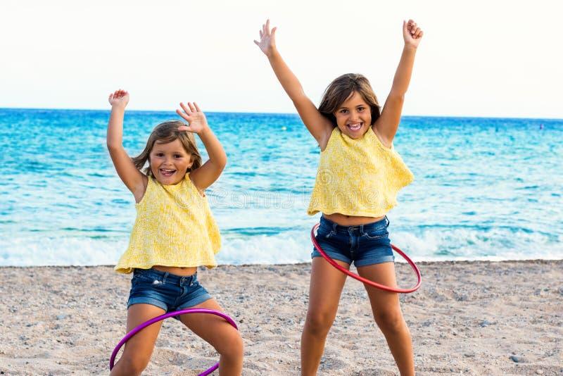 跳舞与在海滩的塑料圆环的逗人喜爱的女孩 免版税图库摄影