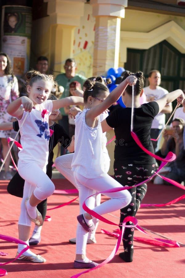 跳舞与在阶段的五颜六色的丝带的女性孩子 免版税库存图片