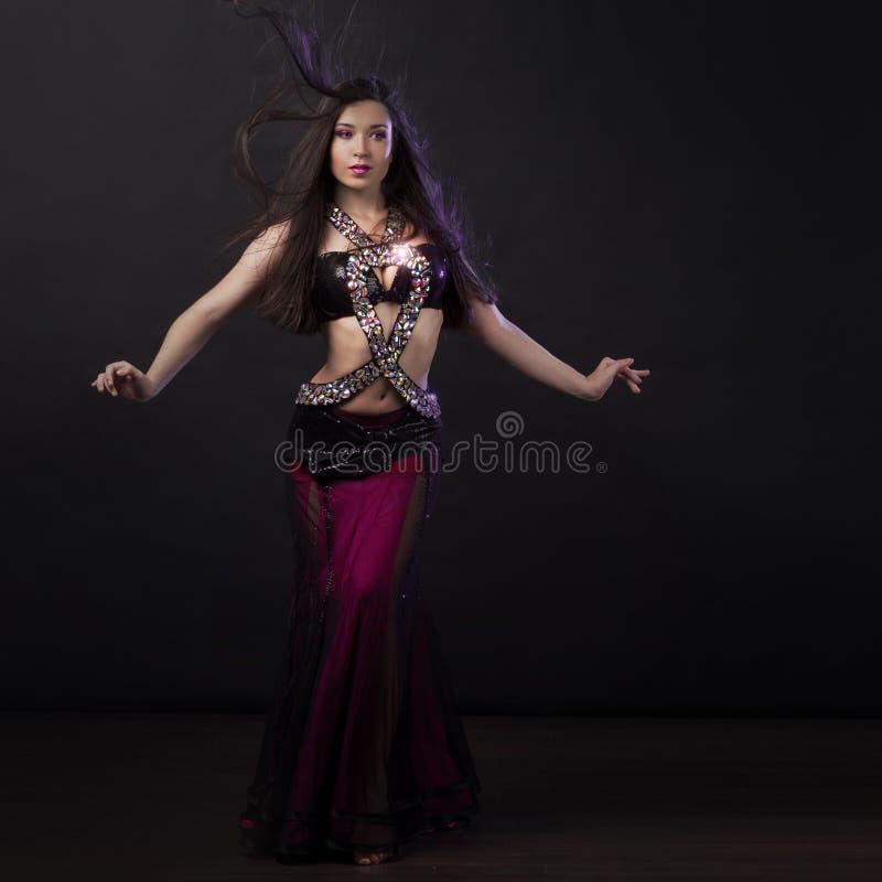 跳舞东方舞蹈的绯红色礼服的美丽的女孩 免版税库存照片