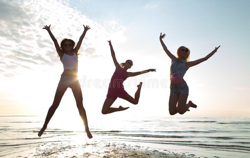 跳舞和跳跃在海滩的愉快的女性朋友 免版税库存图片