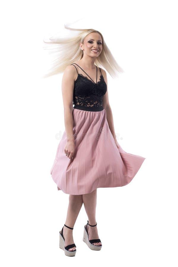 跳舞和转动与流动的头发的夏天衣裳的迷人的年轻白肤金发的妇女 免版税库存照片