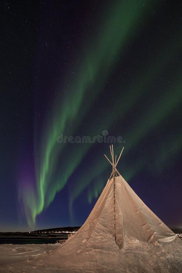 跳舞在一个传统sami帐篷的北极光 免版税库存照片