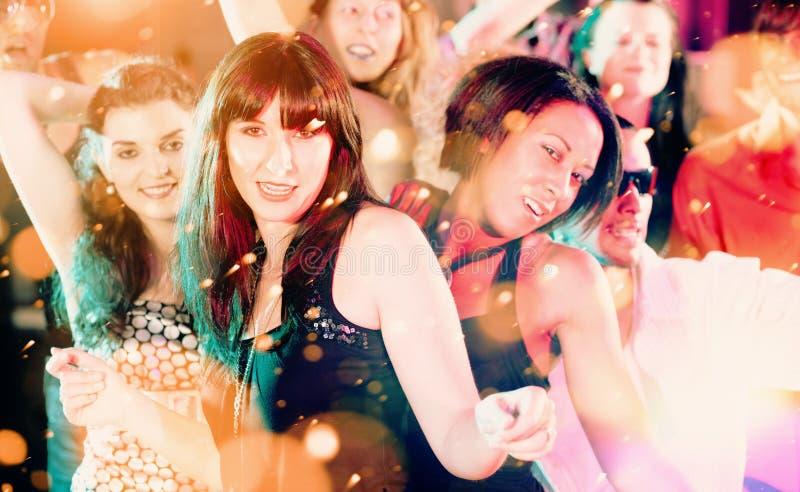 跳舞在俱乐部或迪斯科的妇女和人有党 库存照片