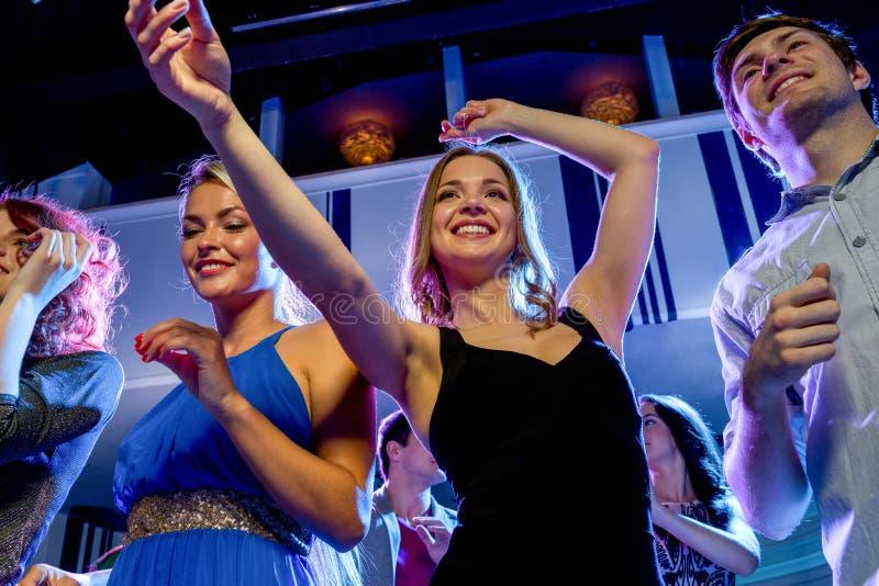 跳舞在俱乐部的微笑的朋友 免版税库存图片