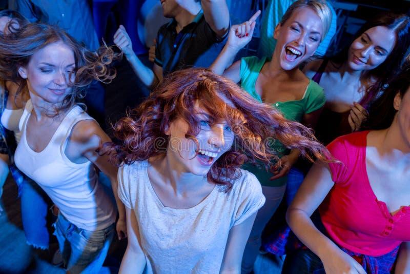 跳舞在俱乐部的微笑的朋友 库存图片