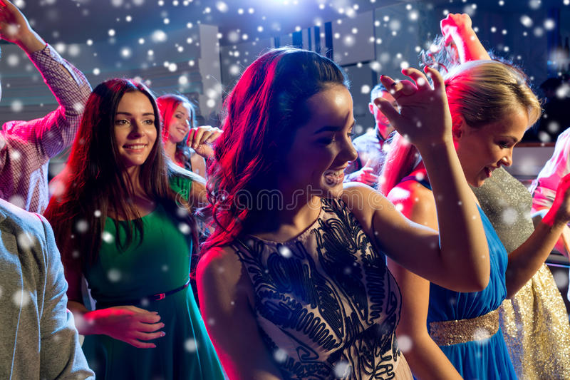 跳舞在俱乐部的微笑的朋友 图库摄影
