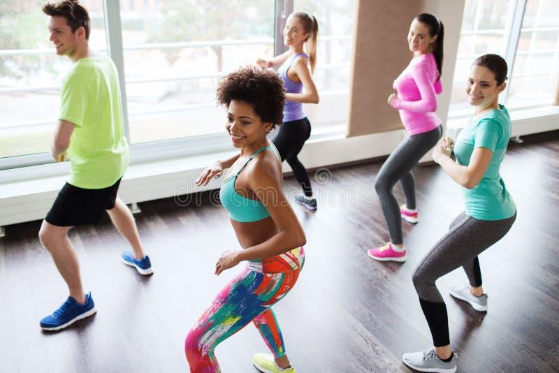 跳舞在健身房或演播室的小组微笑的人民 图库摄影