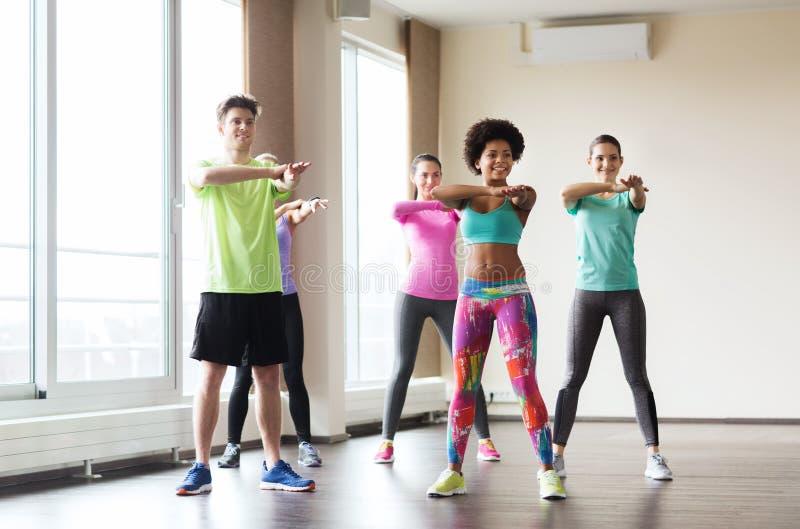 跳舞在健身房或演播室的小组微笑的人民 库存图片