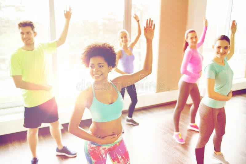 跳舞在健身房或演播室的小组微笑的人民 库存照片