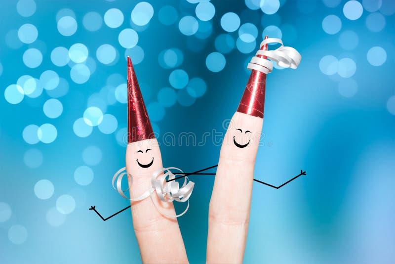跳舞在党bokeh光线影响蓝色背景的两个手指 库存照片