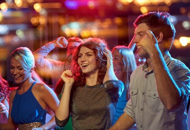 跳舞在夜总会的小组愉快的朋友 免版税库存照片