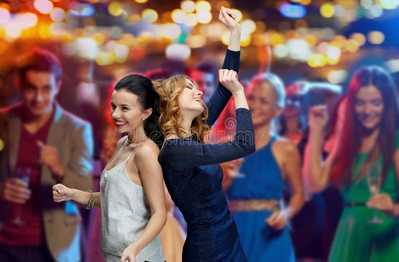 跳舞在夜总会迪斯科的愉快的少妇 免版税库存图片