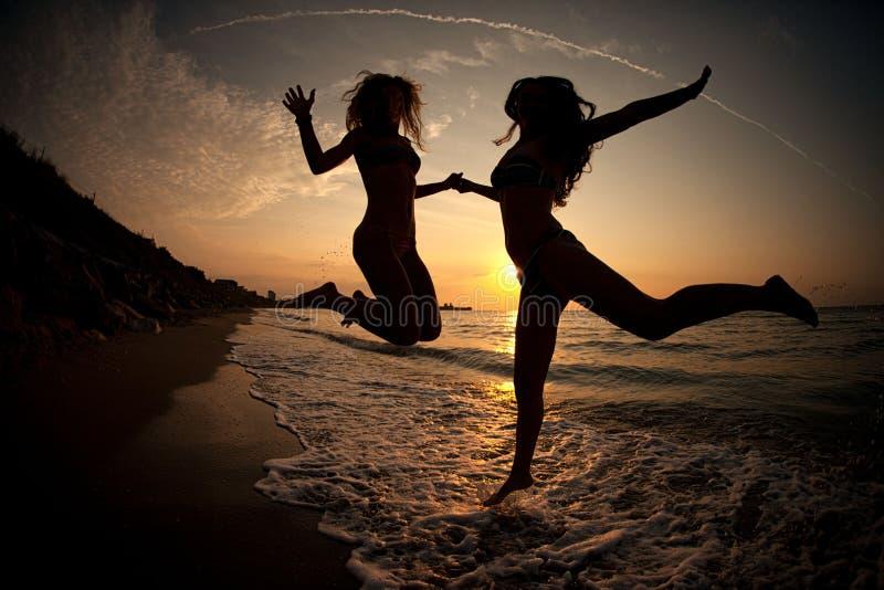 跳舞在海的日落的女孩 库存图片