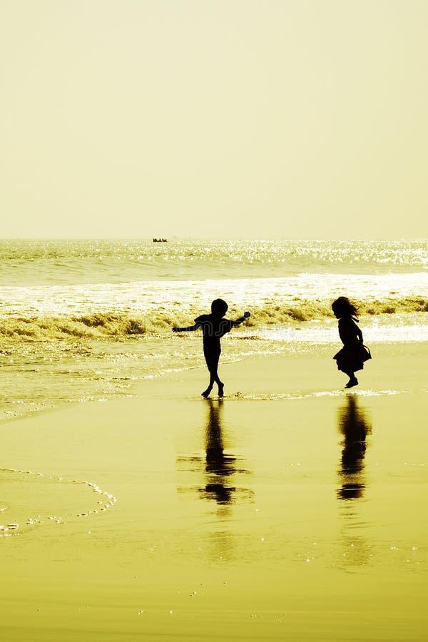 跳舞在海滩的两个孩子在日落 免版税库存图片