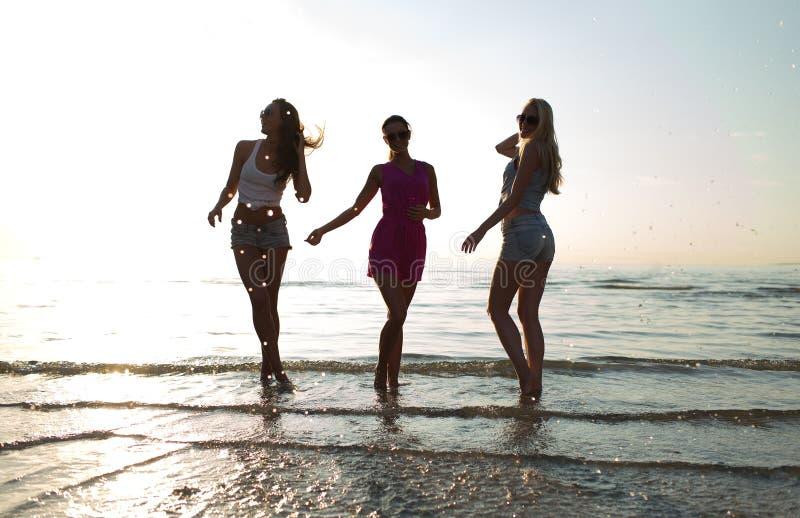 跳舞在海滩的愉快的女性朋友 库存照片