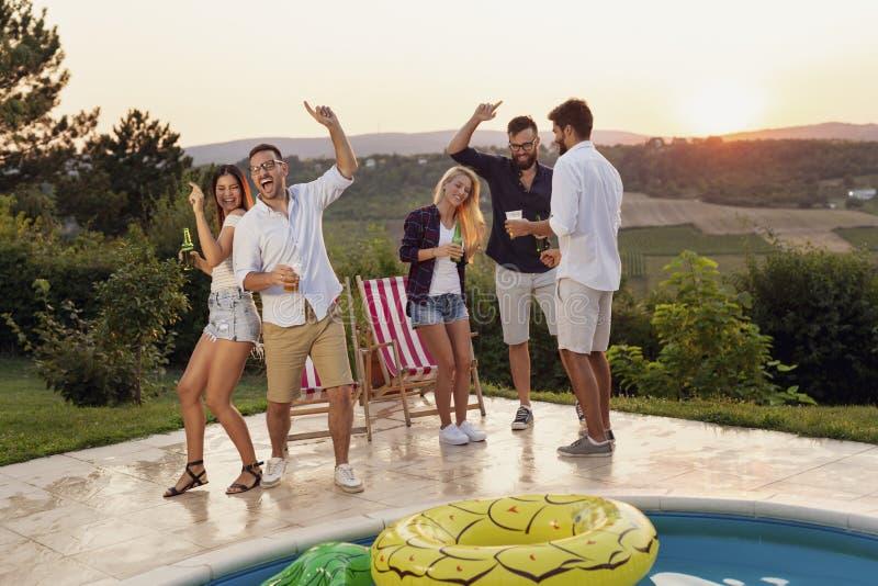 跳舞在游泳池边党的朋友 免版税图库摄影