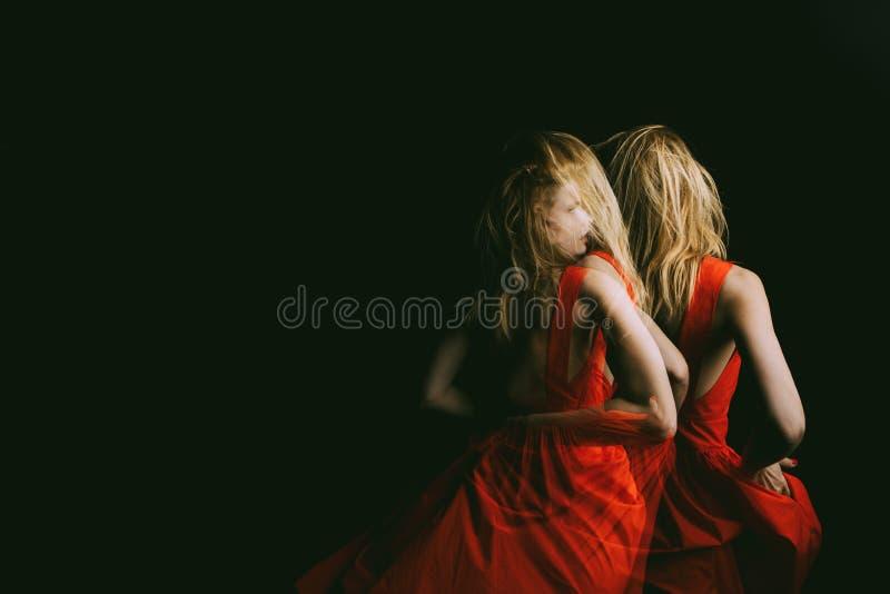 跳舞在猩红色红色礼服的黑暗的妇女 三倍曝光 概念性原始的创造性的情感照片隐喻 图库摄影