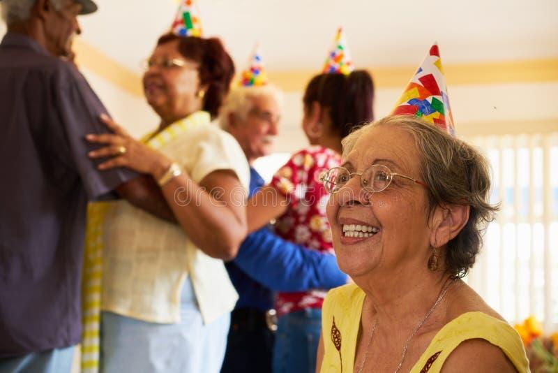 跳舞在生日聚会的资深朋友在招待所 免版税库存照片