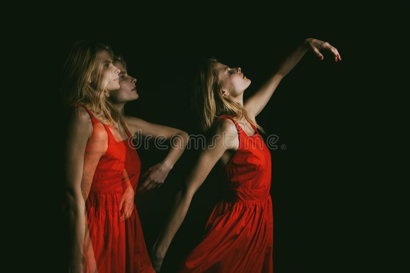 跳舞在红色礼服的黑暗的妇女灵魂在黑背景 三倍曝光 概念性原始创造性 库存图片