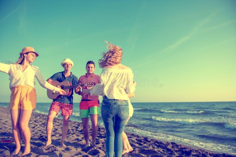 跳舞在美丽的su的海滩的小组愉快的青年人 免版税库存照片