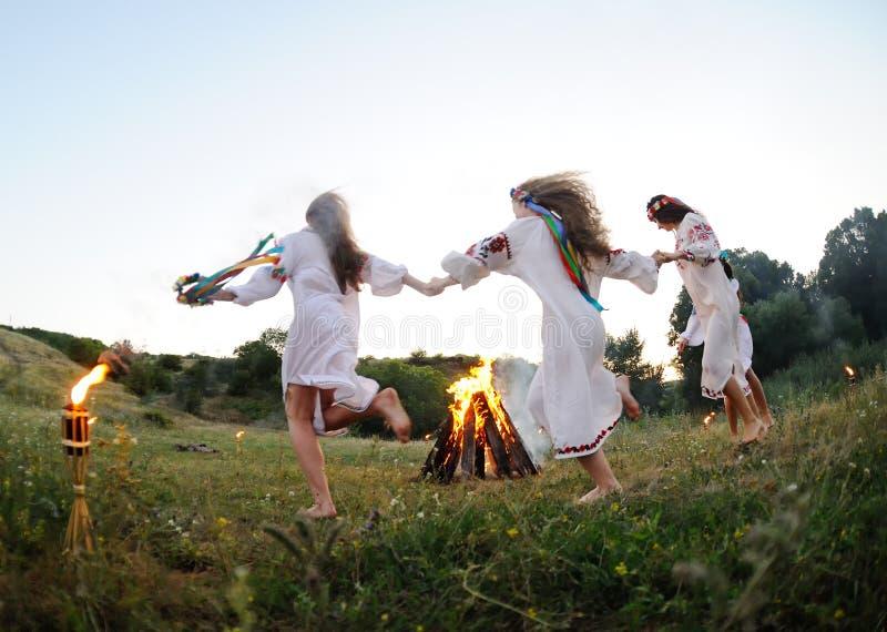 跳舞在营火附近的乌克兰全国衬衣的女孩 Midsumer 免版税库存照片