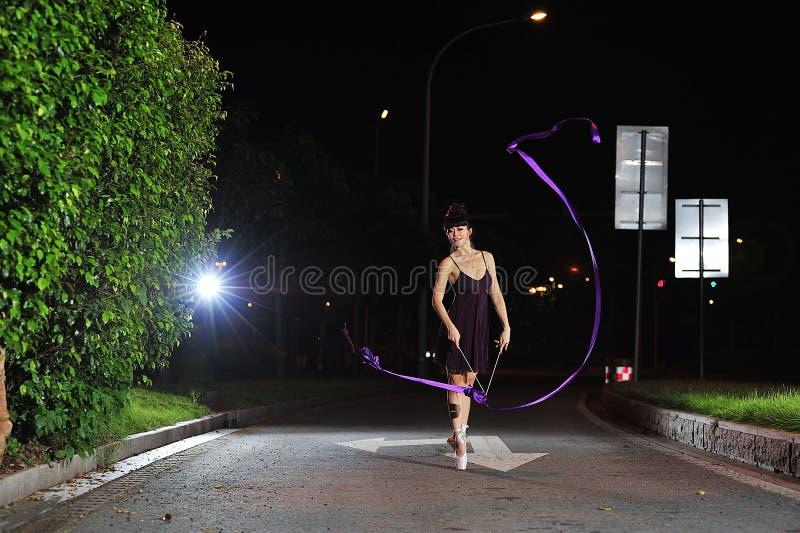 跳舞在路的亚裔女孩芭蕾在晚上 免版税库存图片