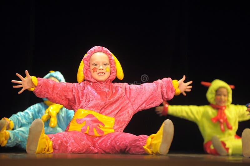 跳舞在阶段的滑稽的色的总体外籍人的孩子 库存照片