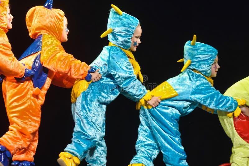 跳舞在阶段的滑稽的色的总体外籍人的孩子 免版税库存图片