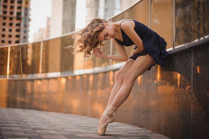 跳舞户外在一个现代环境里的年轻美丽的芭蕾舞女演员 芭蕾舞女演员项目 免版税库存照片