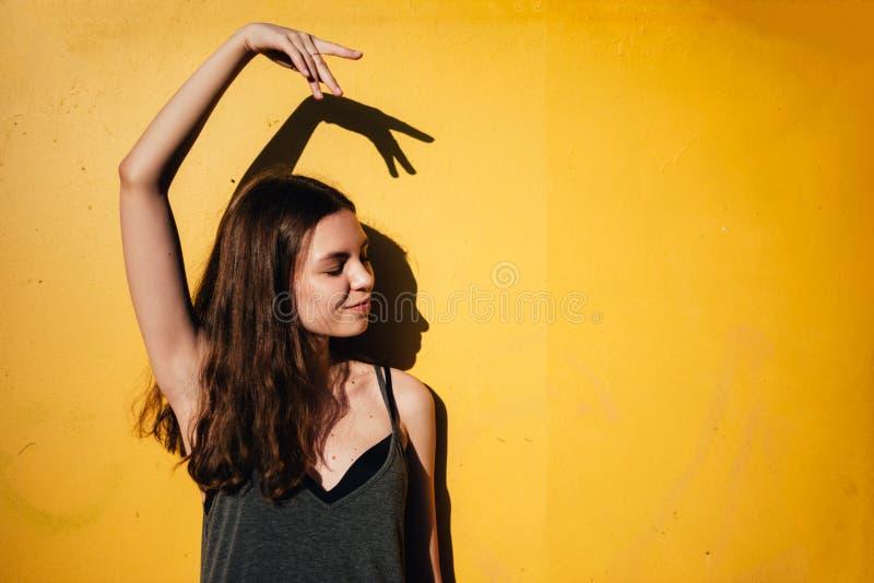跳舞户外在黄色墙壁背景的青少年女孩在市区 免版税库存照片