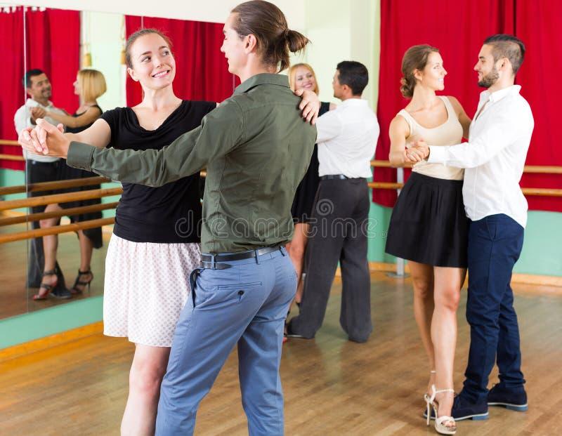 跳舞探戈的三对愉快的夫妇 图库摄影