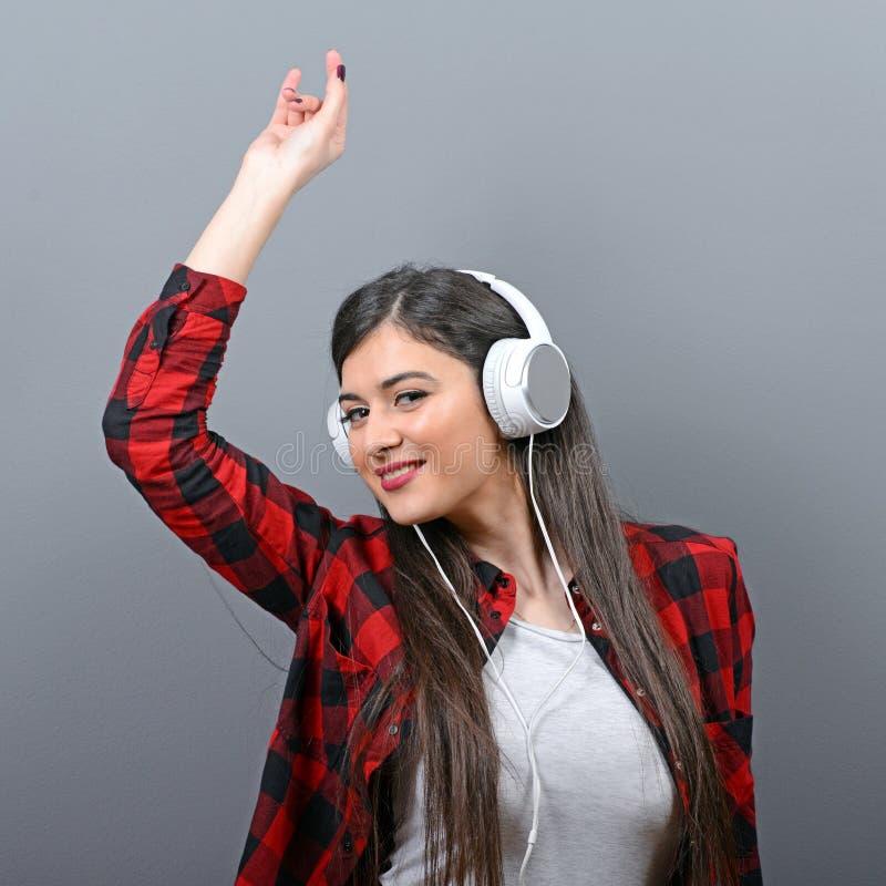 跳舞有耳机的都市妇女画象反对灰色背景 免版税库存照片