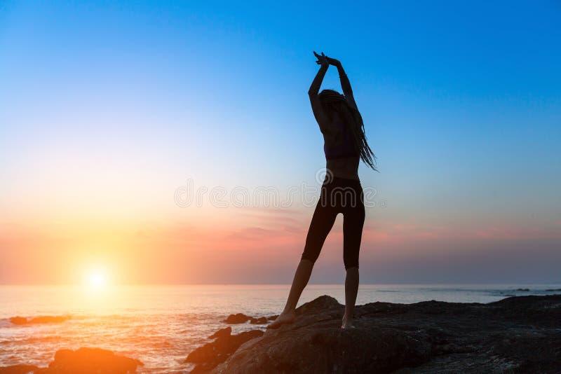 跳舞海洋海岸的年轻亭亭玉立的妇女剪影在日落期间 免版税库存照片