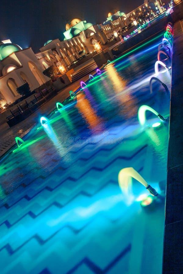 跳舞的多色的喷泉在晚上 免版税库存图片