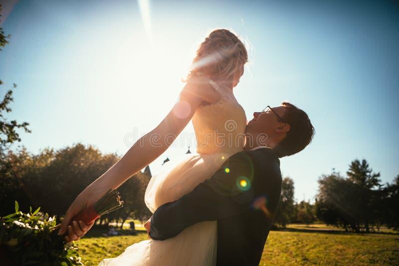 跳舞的年轻新娘和新郎阳光背景 免版税库存图片