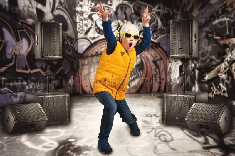 跳舞节律唱诵的音乐的男孩 儿童` s时尚 年轻交谈者 在墙壁上的街道画 冷却斥责dj 库存照片