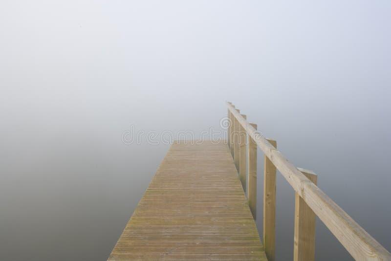 跳船消失入薄雾被盖的湖 库存照片