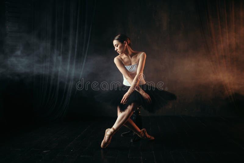 跳芭蕾舞者坐黑人行道 库存照片