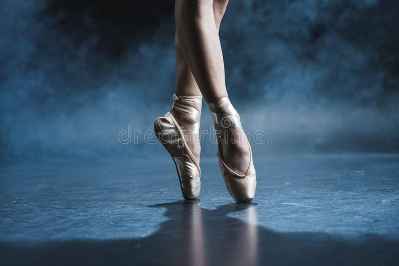 跳芭蕾舞者播种的看法在pointe鞋子的在黑暗的演播室 免版税库存照片