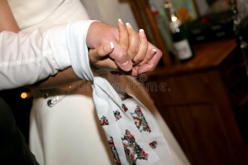 跳起一起婚姻的毛巾新娘和新郎 库存照片
