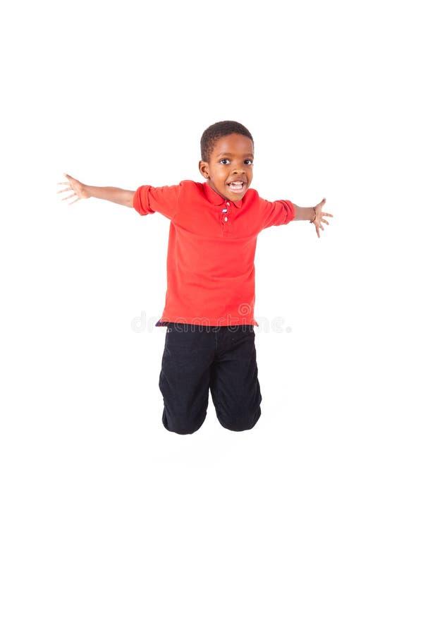 跳跃一个逗人喜爱的非裔美国人的小男孩的画象,被隔绝 免版税库存照片