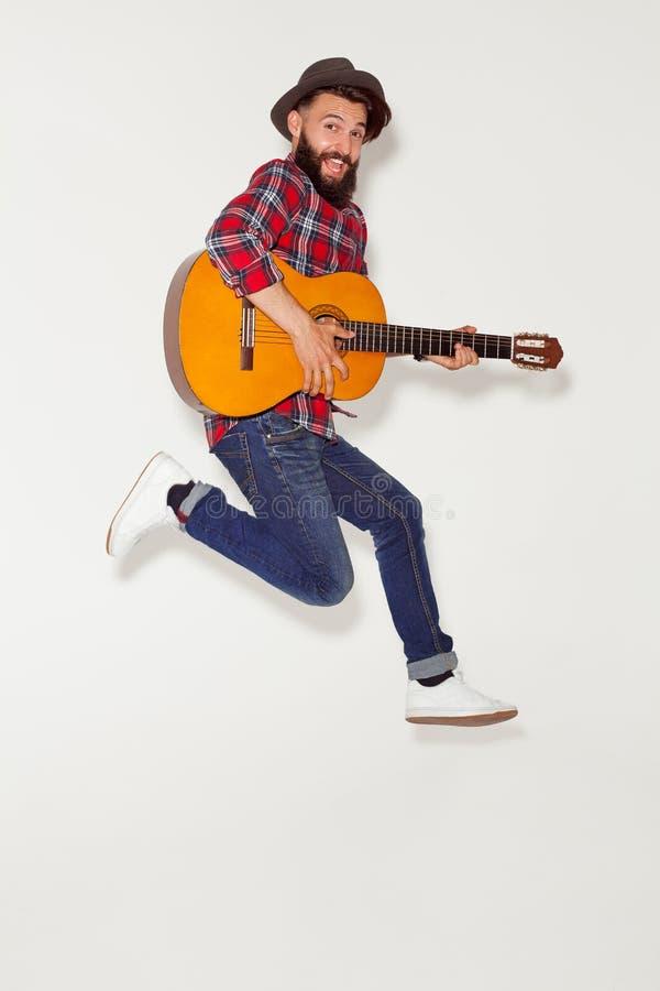跳跃与吉他的精力充沛的人 库存图片