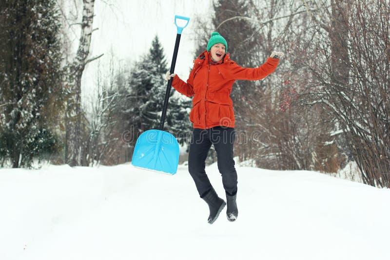 跳跃与在农村路的雪铁锹的滑稽的年轻女人 冬天季节性概念 免版税图库摄影