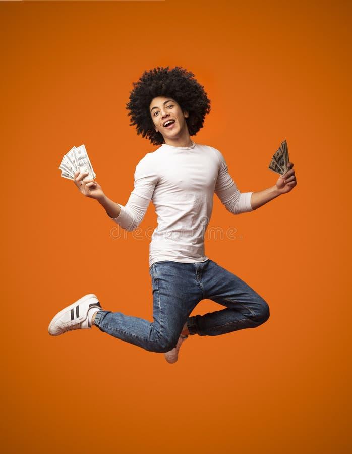 跳跃与在橙色背景的金钱的激动的年轻人 免版税库存照片