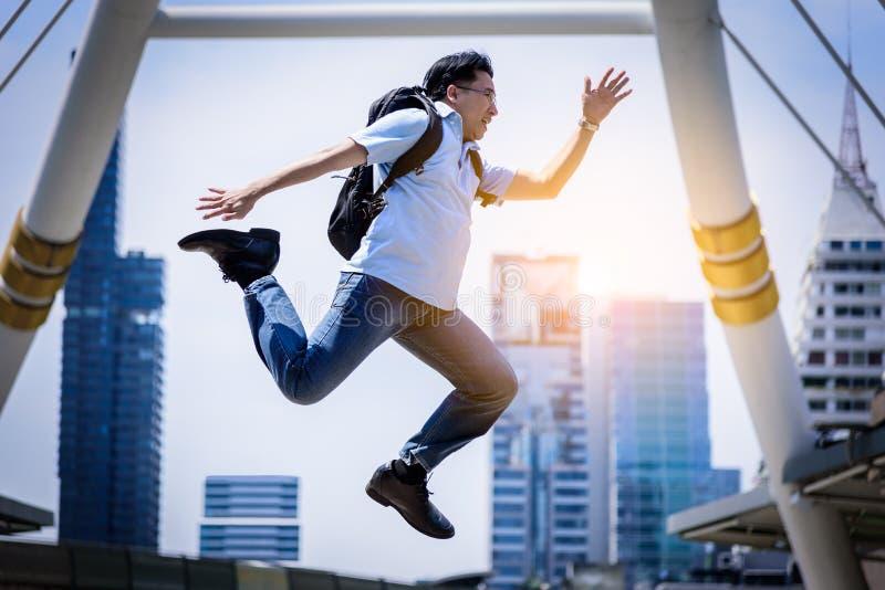 跳跃与大厦和都市风景背景的亚洲商人 免版税库存照片
