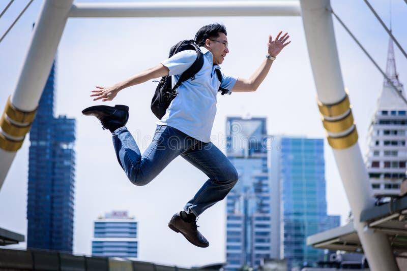 跳跃与大厦和都市风景背景的亚洲商人 免版税图库摄影