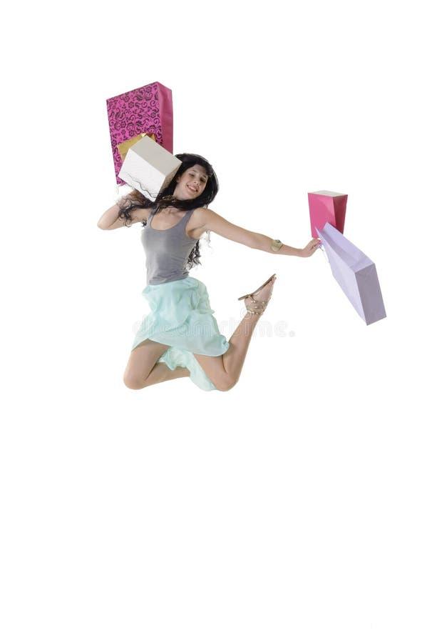 跳跃与她的购物小包的年轻愉快的女孩 免版税库存照片