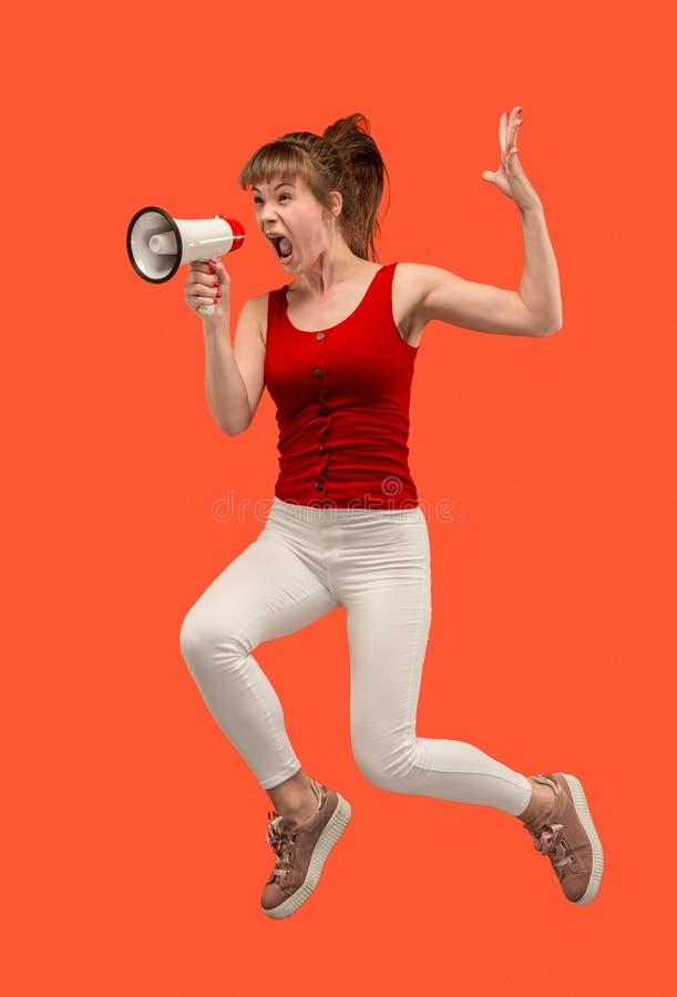 跳跃与扩音机的美丽的少妇被隔绝在红色背景 免版税图库摄影